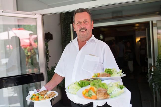 Ein Kellner trägt drei Teller mit Essen zu den Gästen