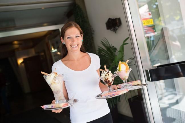Eine Kellnerin trägt drei große Eisbecher auf einen Tablett